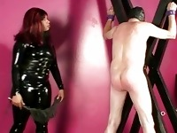Black domina spanks and whips suspended male slave