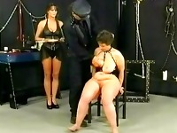 Fat slave with large tits gets spanked on her bald pussy by